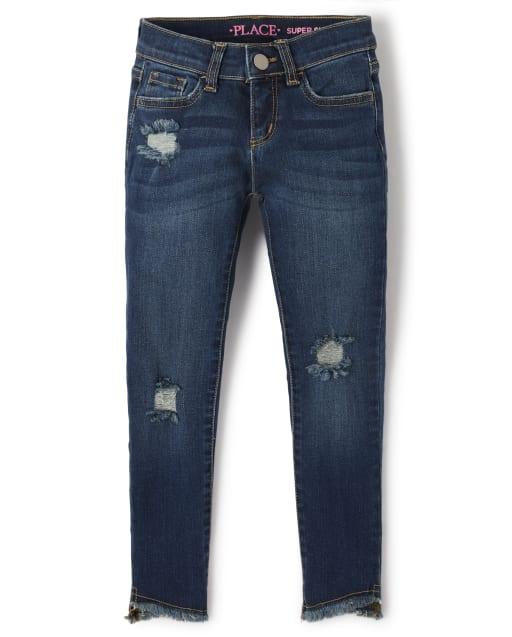 Jeans super skinny de mezclilla desgastada con dobladillo tulipán